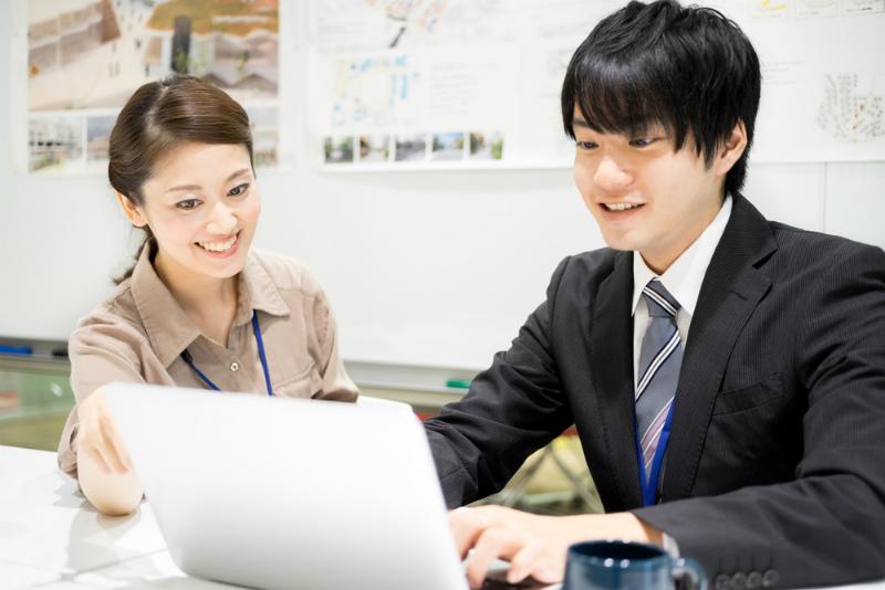パソコンで作業するビジネスマンとレクチャーする女性