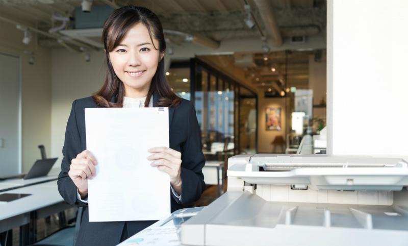 書類を両手に持つ若い女性