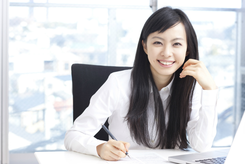 ペンを持つ笑顔の女性