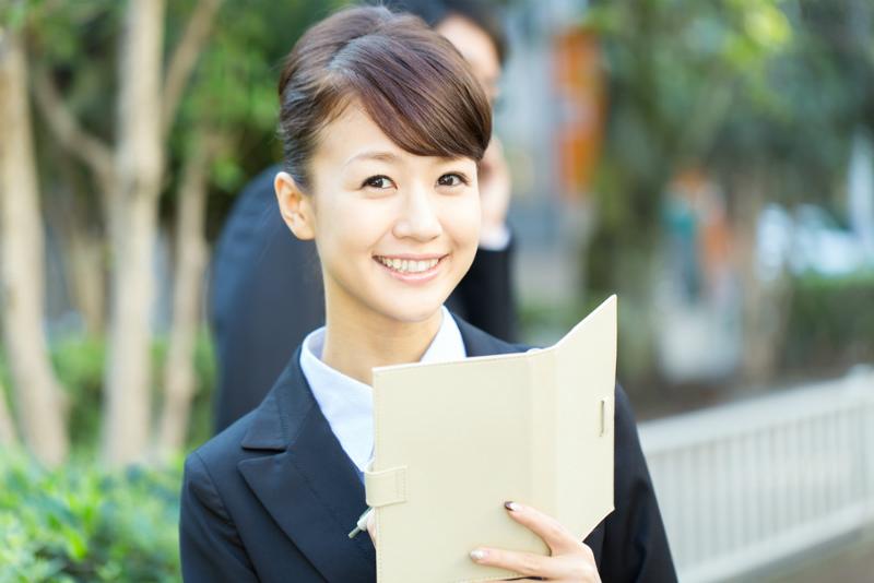 手帳を持つ笑顔の女性