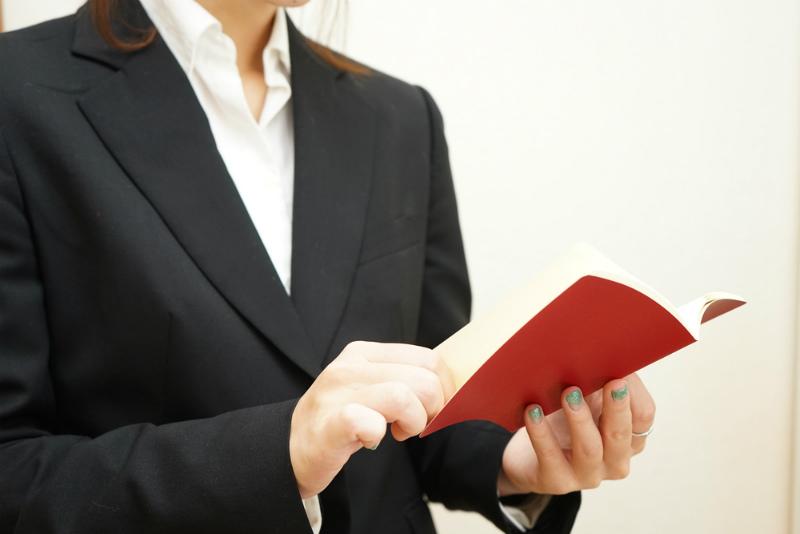 手帳を開くスーツ女性の手