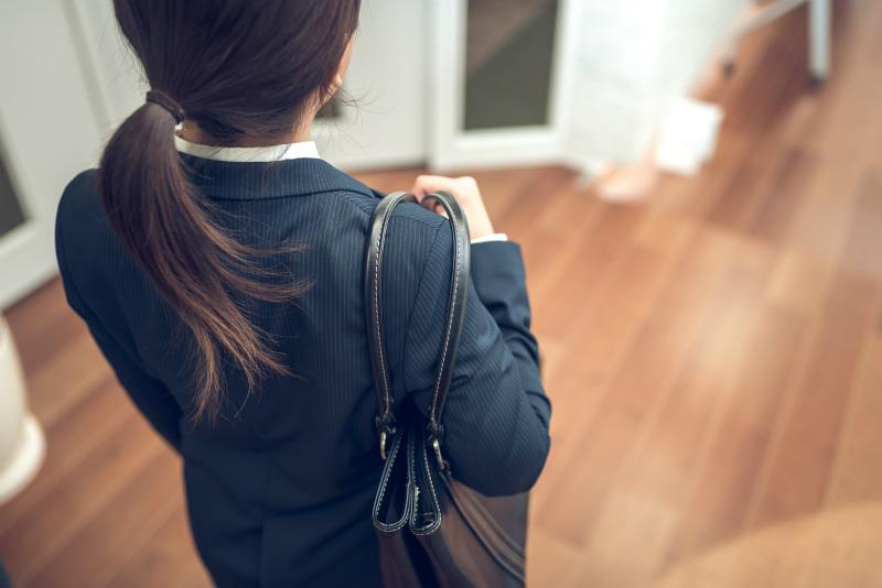 鞄を持つスーツ姿の女性