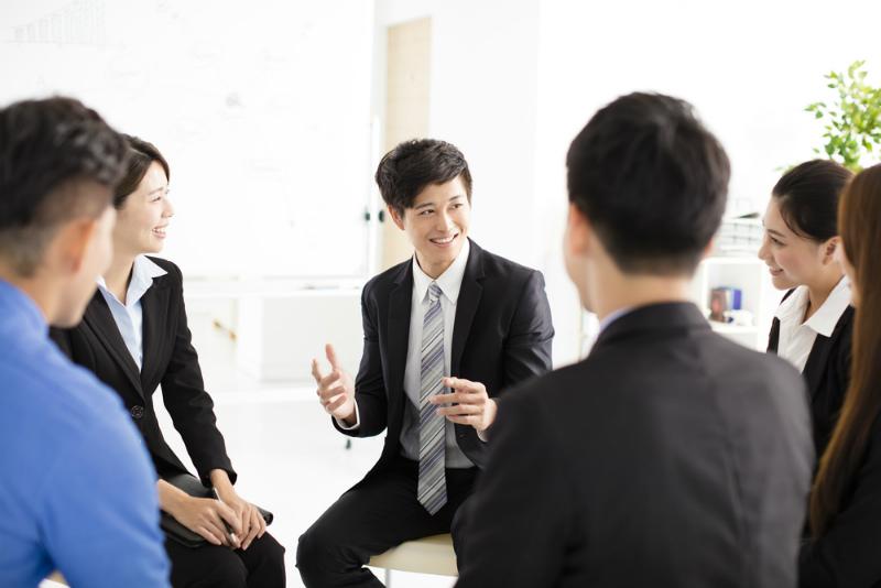 複数人で会話するビジネスマン