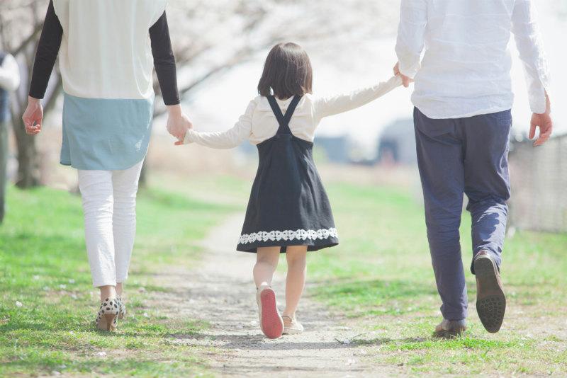 手を繋いで歩く家族