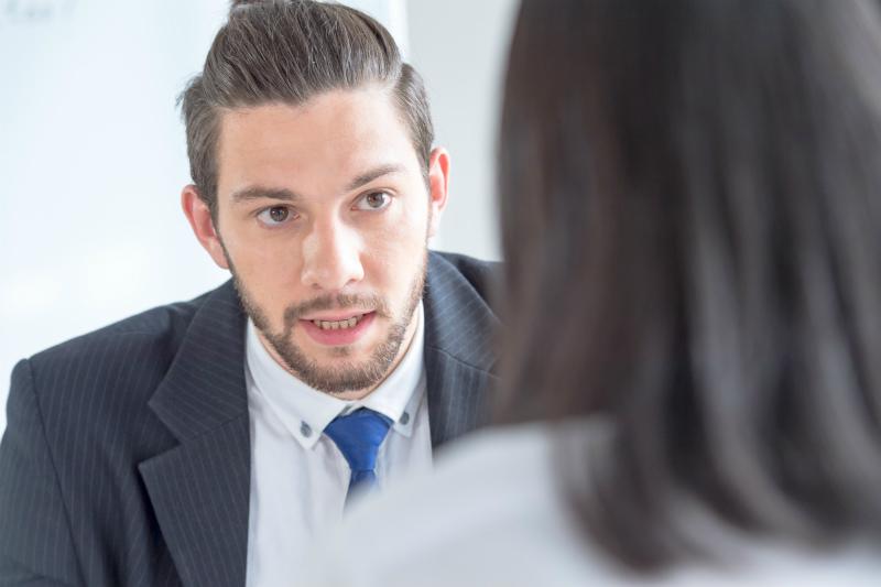 外国人男性と話している日本人女性の後ろ姿
