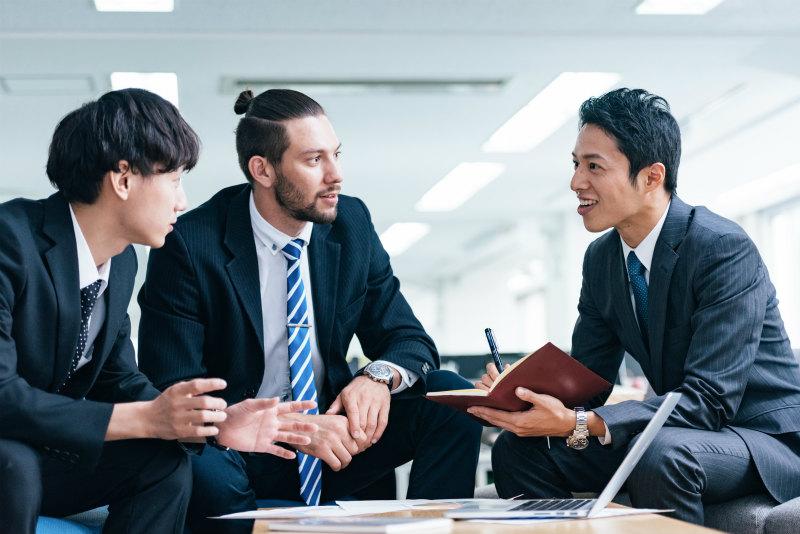 オフィスで話し合っている日本人男性と外国人男性
