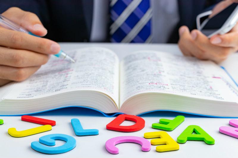 スマホ片手に辞書で英語を勉強するビジネスマン