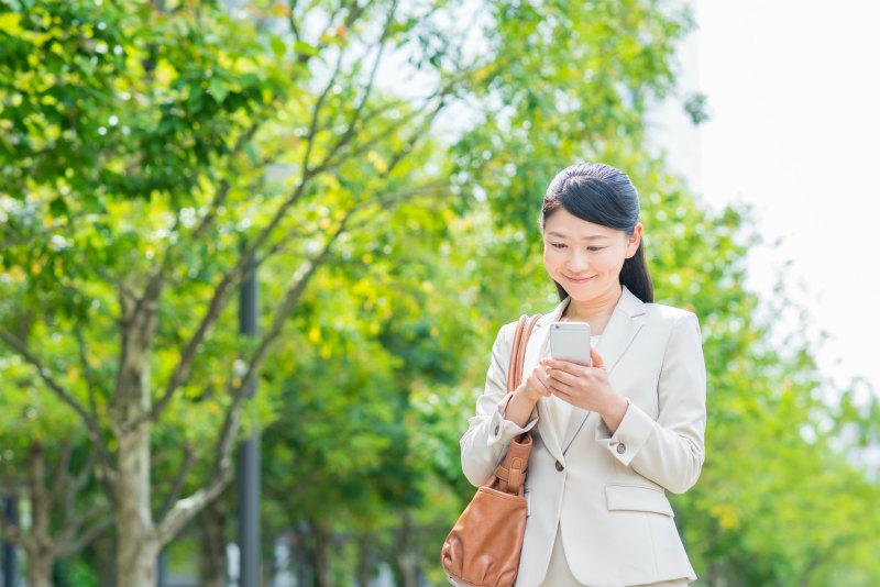 笑顔でスマートフォンを操作する女性