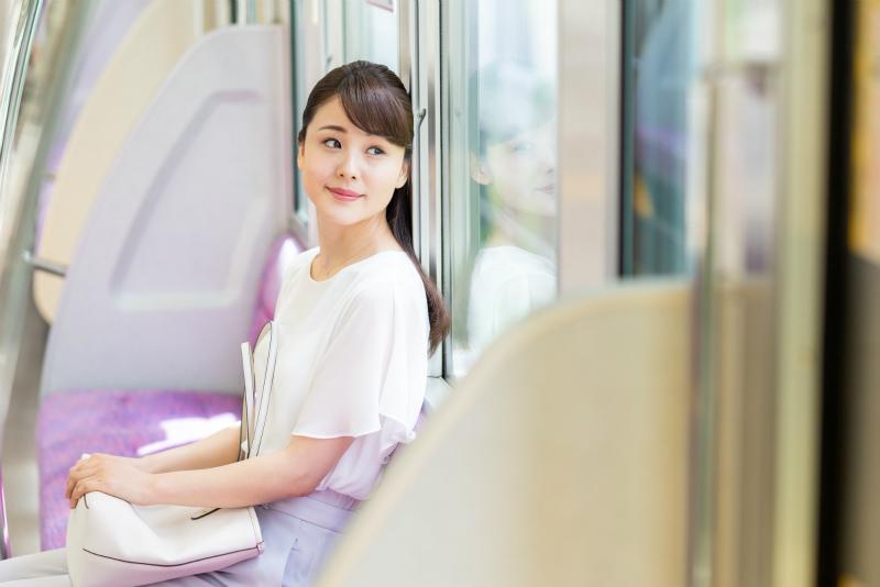 電車の窓から外を見る女性