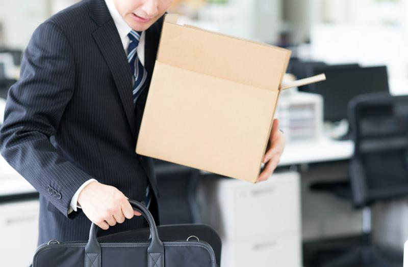 デスクの荷物を整理している若い男性