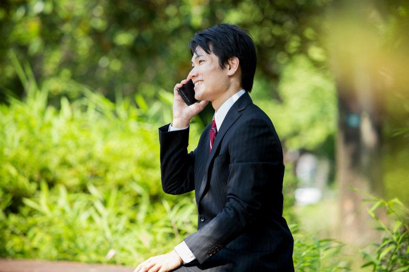 屋外で電話しているスーツ姿の若い男性