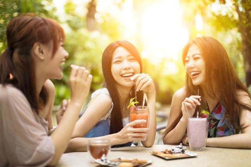 カフェで談笑する若い女性グループ