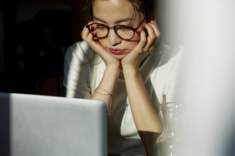 頬杖をついてパソコンを眺める若い女性