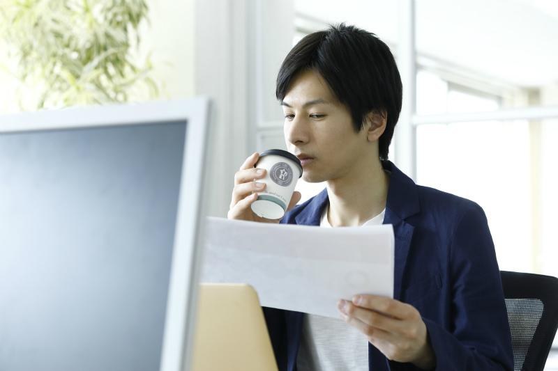 コーヒーを片手に資料を眺めている若い男性