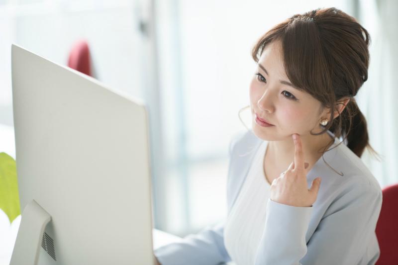 デスクトップPCを見つめる女性