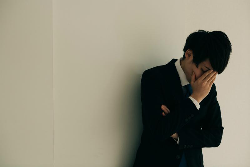 顔を両手で覆っているビジネスマン