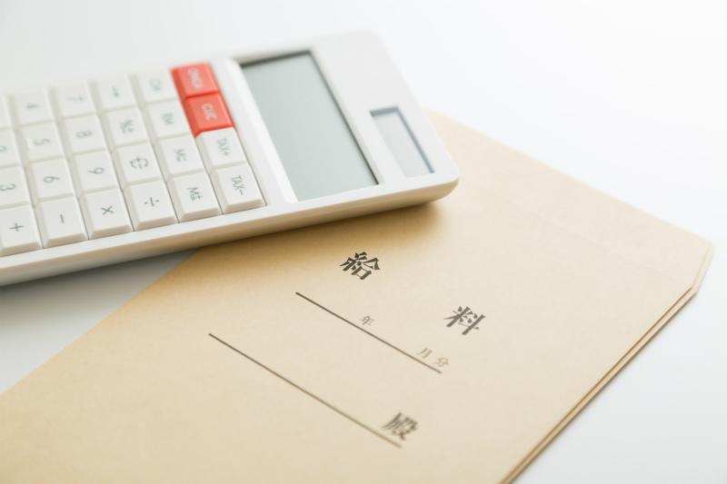 給料袋と電卓が机に置かれている様子