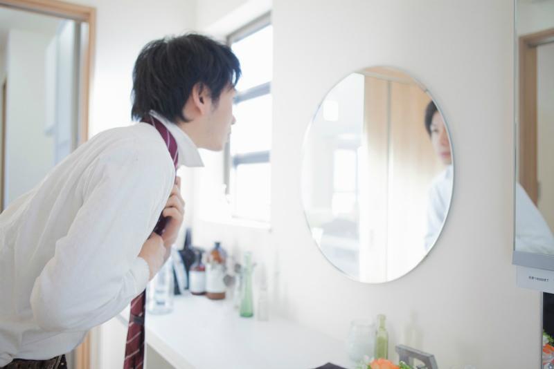 49-2【新卒面接との違い2:求められる服装が違う!】鏡を見ながらネクタイを結ぶ男性