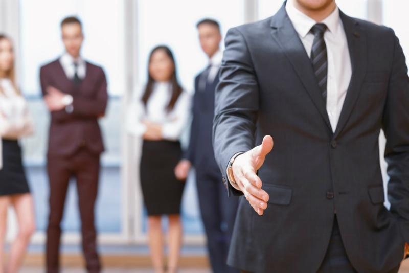 49-5【まとめ】握手を求めるスーツの男性と背後に複数のビジネスパーソン