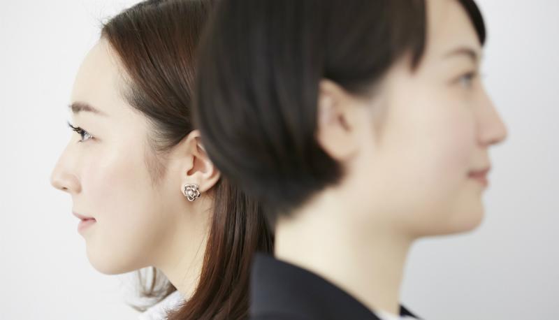背中合わせに立っている2人の女性