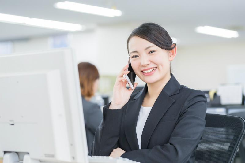 オフィスのデスクで電話をかけている女性