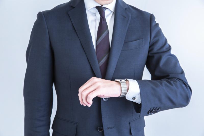 腕時計を見ているスーツ姿の男性