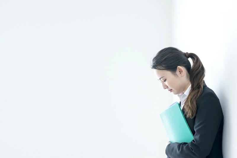 ファイルを抱えて俯いている女性