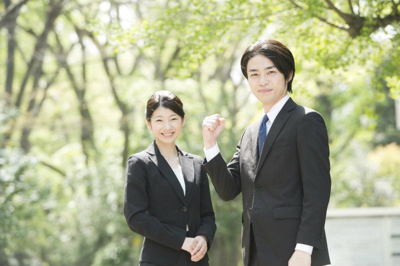 緑の多い屋外で立っている2人の若い男女
