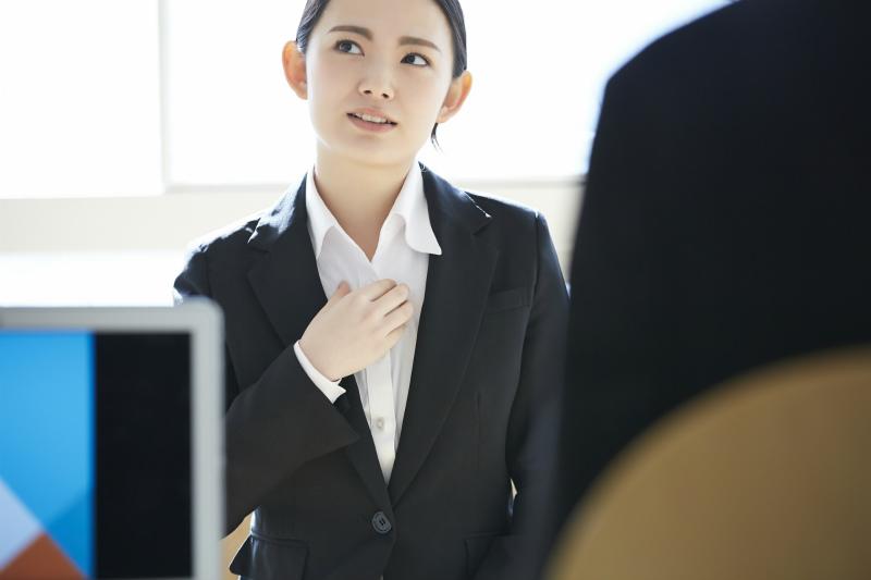 考えながらしゃべる様子のスーツ姿の女性