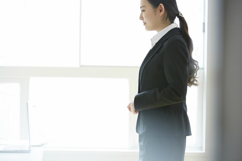 スーツを着て立っている若い女性