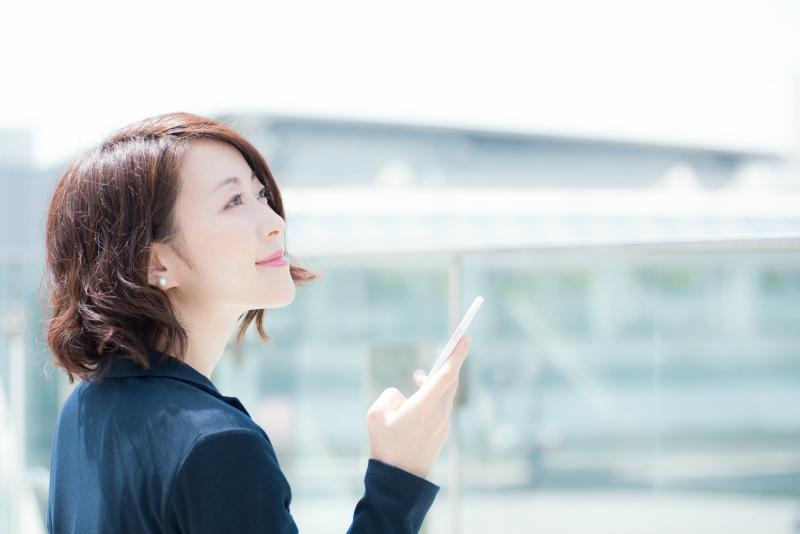 スマホを片手に空を見上げる女性