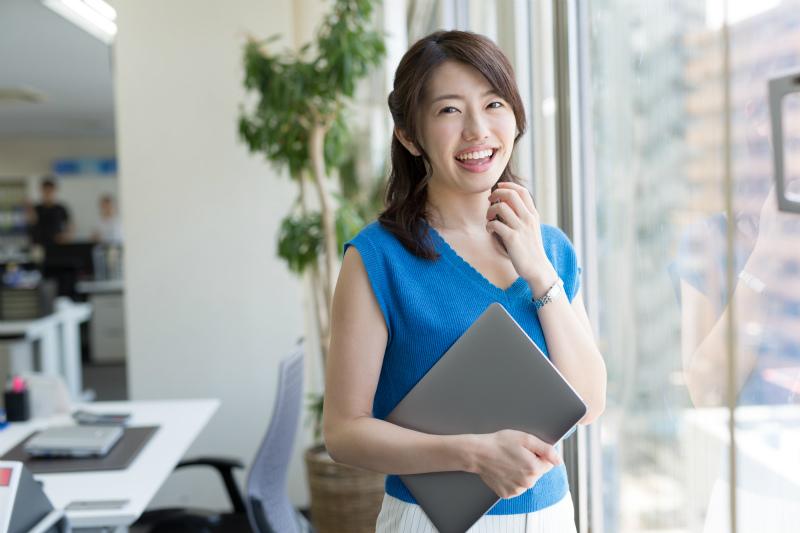 ノートパソコンを片手に笑顔を見せる女性