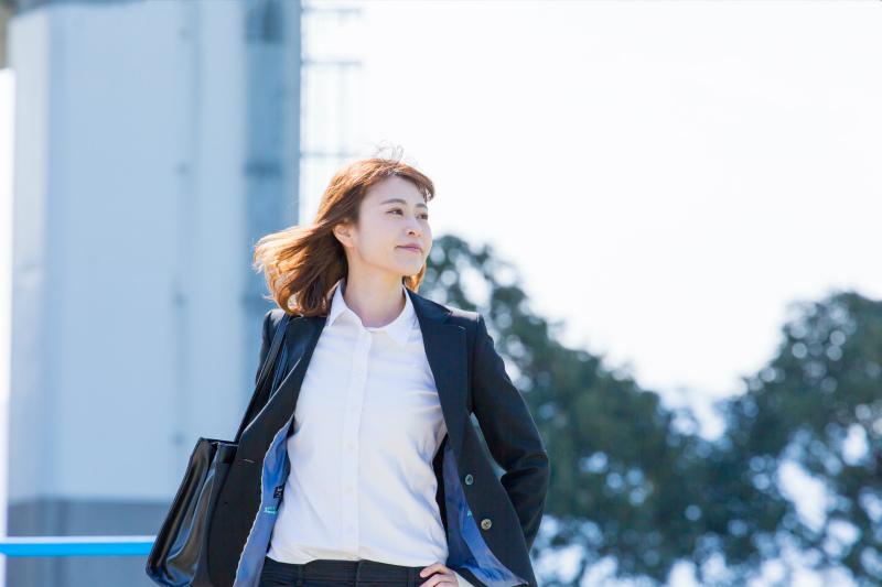 屋外を歩いているスーツ姿の若い女性