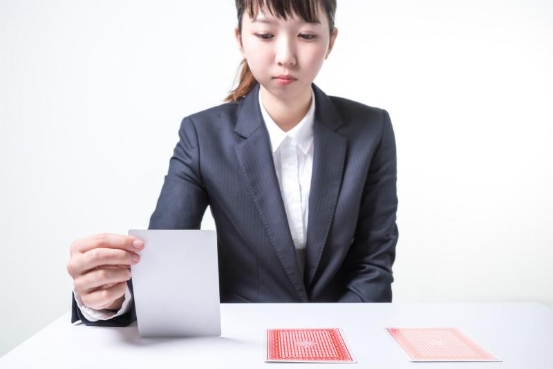 三枚のカードを前に悩むスーツ姿の女性