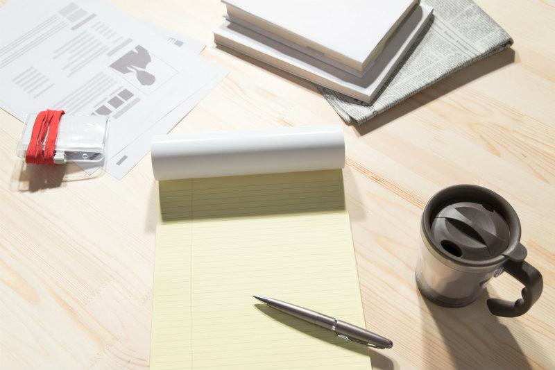机の上にノートやコップが置かれている様子