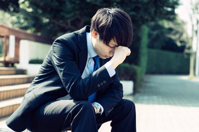 悩む様子のスーツの男性