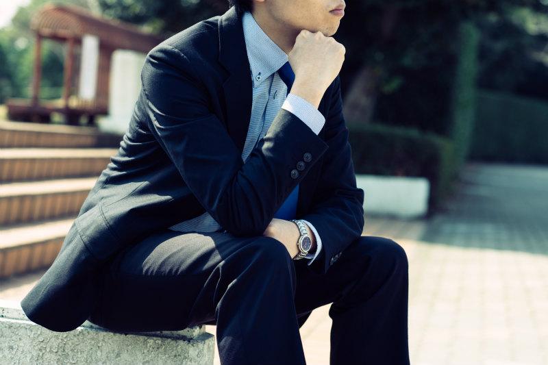 何かを考えるスーツの男性