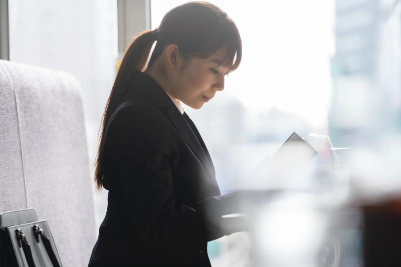 カフェでノートを開いている転職活動中の女性