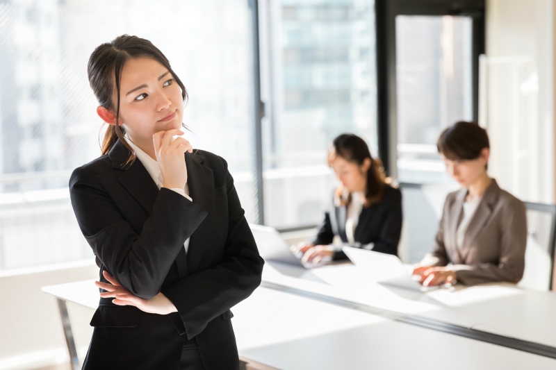 パソコンを見ている2人のビジネスウーマンと、その近くで考え込む若い女性