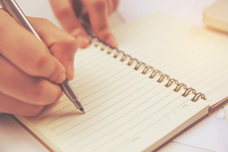 女性がノートに何かを書き込んでいる様