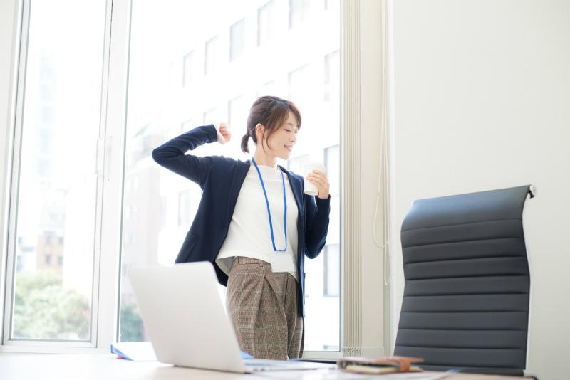 オフィスでコーヒーを飲みながらくつろぐ女性