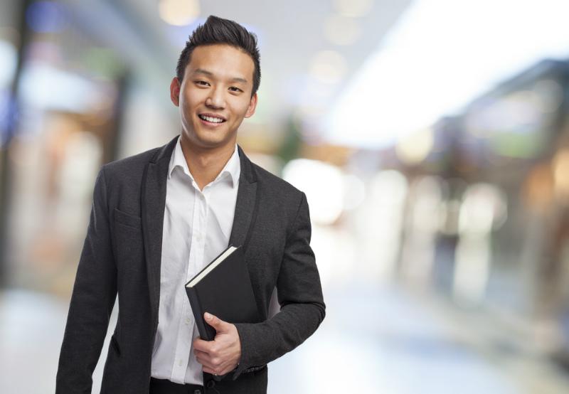 ビジネス手帳をわきに抱える若いビジネスマン