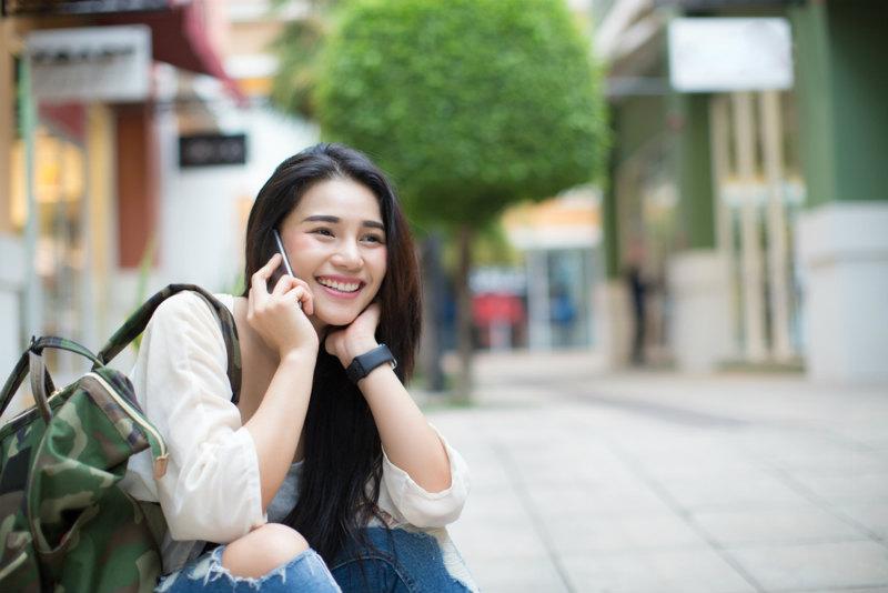 電話する笑顔の若い女性