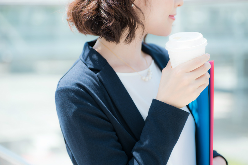 コーヒーを片手に何かを見つめる女性