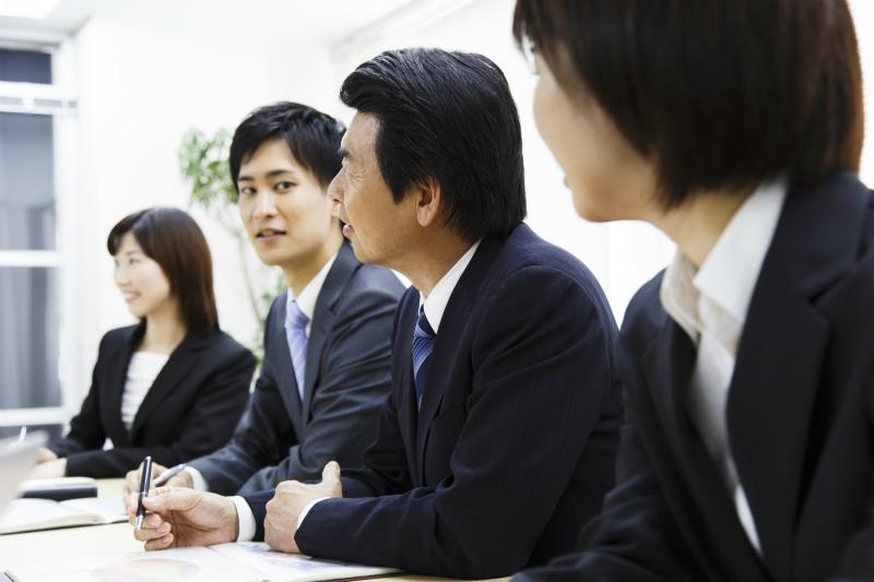 会議で発言する役職者を見つめる若手社員