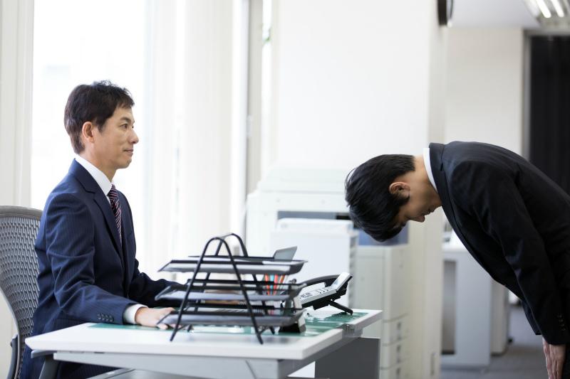 上司に頭を下げる部下