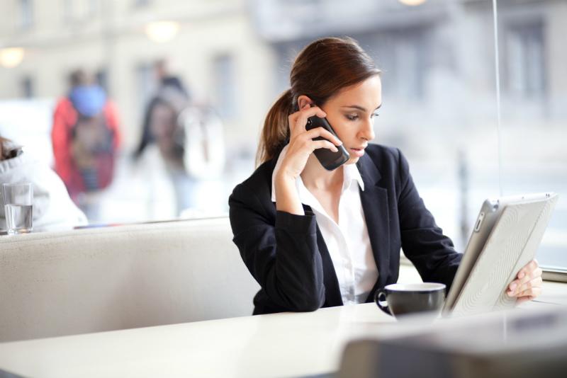 電話しながらタブレットを見つめる女性