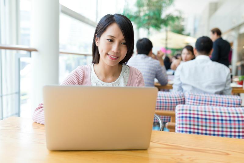 パソコンを眺める笑顔の女性