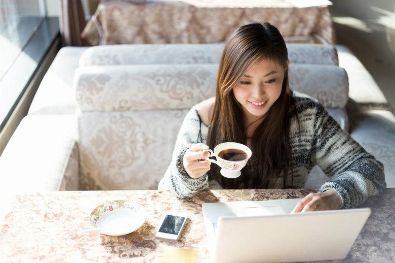パソコンを見つめてコーヒーを飲む女性