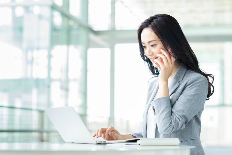 パソコンを見ながら電話する女性